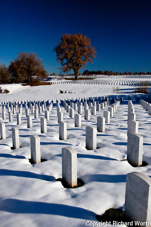 Blue Colorado sky over white snow surrounding white granite headstones at Fort Logan National Cemetery, Denver, Colorado.