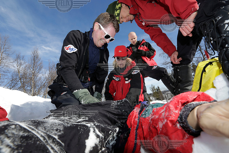 """Crew from Norwegian Air Ambulance practice rescue skills at Camp Torpomoen, a training facility..An avalanche viciitm, in the form of a dummy, is being """"resuscitated"""" . by doctors and rescue paramedic. ..Bjarne Vikenes,  Ranveig Falkevik, Harald Bettum. Pilot Marius Malmo in background"""