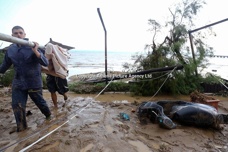 Locals clear debris from the beach in Agia Triada