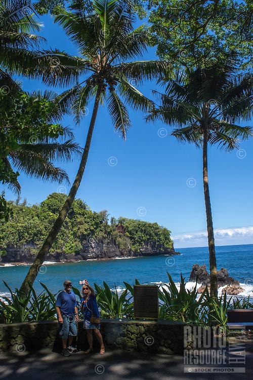 Tourists with a selfie stick pause on a trail through Hawaii Tropical Botanical Garden at Onomea Bay to take photos, Hamakua coastline, Big Island of Hawaiʻi.