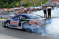 Jun. 16, 2012; Bristol, TN, USA: NHRA pro stock driver Jason Line (near lane) burns out alongside his teammate Greg Anderson during qualifying for the Thunder Valley Nationals at Bristol Dragway. Mandatory Credit: Mark J. Rebilas-