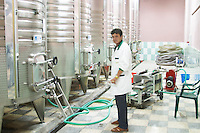 Stainless steel fermentation and storage tanks with cooling coils on the outside. Winery worker standing in front of a filter. Kantina Miqesia or Medaur winery, Koplik. Albania, Balkan, Europe.