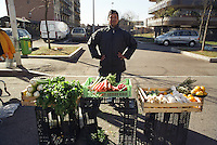Milano, mercato rionale al quartiere Bruzzano, periferia nord. Immigrato filippino laureato in ingegneria meccanica vende verdura --- Milan, local market at Bruzzano district, north periphery. Immigrant from Philippine with a degree in automotive engineering selling vegetables