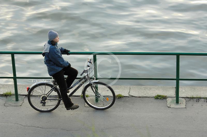 Poland, Krakow, Man on bicycle, resting on railing at riverside