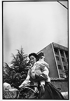 A mother grimaces as she carries her child on her shoulder while riding with one hand in Beijing...PHOTO BY WANG TONG / SINOPIX