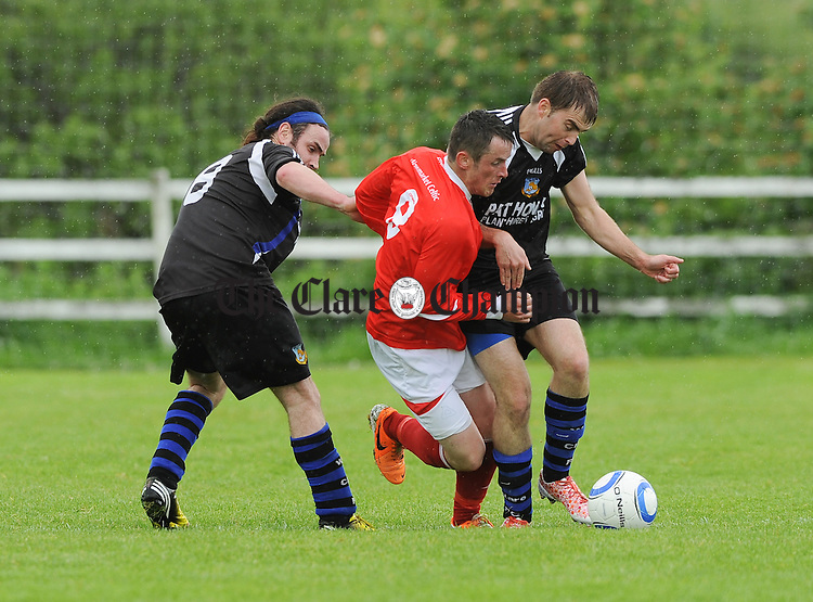 Ronan Mc Cormack of Newmarket Celtic A in action against Brian Harte and Terry Hirlihy of West Clare FC during their Cup semi final game at Doora. Photograph by John Kelly.