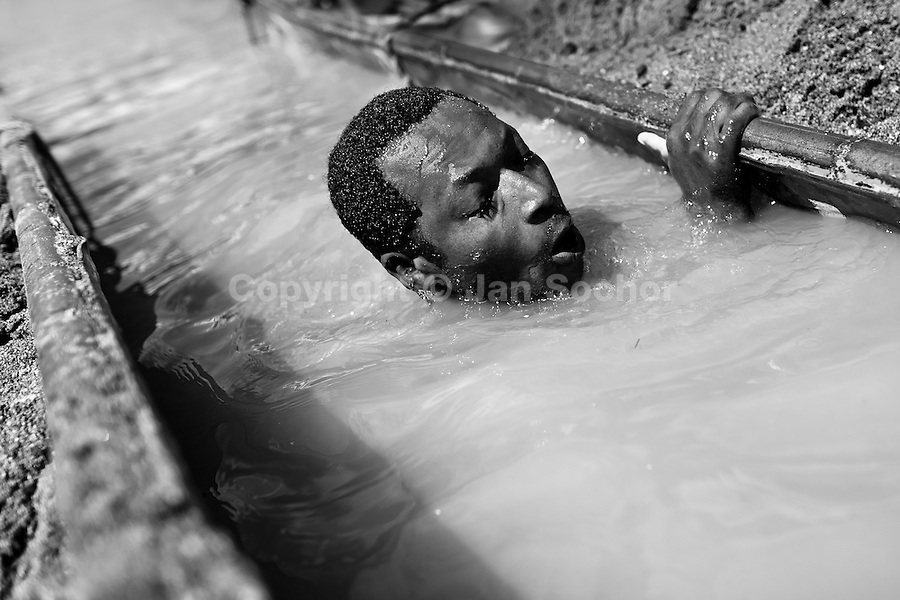 A Colombian sand miner dives under the water to extract sand from the bottom of the river La Vieja in Cartago, Colombia, 10 December 2013. Artisanal (unmechanised) sand mining is an ancient mining technique used to obtain sand for construction purposes. Depending on the natural conditions (strength of the stream, depth of the river etc.), together with the sand miners' physical condition, the material is extracted in metal buckets, either by standing on the river bottom and searching for sand by feet, or, diving up to 3-5 meters deep using a wooden plank with steps. In spite of the physically demanding work, a sand miner's daily salary does not exceed 15-20 US dollars. However, the sand miners are very proud of their profession, valuing their work freedom above all, and usually, as long as their health and strength permit, they keep facing the river stream.