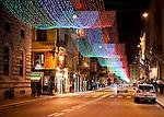 Draped light strings in colors of the Italian flag illuminate the Via del Corso at night.  (Rome, Italy)