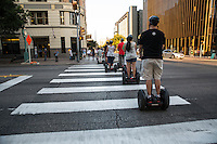 A Segway Tour group crosses the street at Congress at 6th Street on their downtown Austin sightseeing tour.