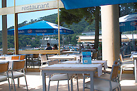 Restaurant outside seating terrace. Reflections in a big window of the sea, hotels, people sitting. Hotel and restaurant Kompas. Dubrovnik, new city. Dalmatian Coast, Croatia, Europe.