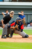 Greeneville Astros catcher Alfredo Gonzalez (23) checks the runner at first base as home plate umpire Ronnie Whiting looks on during the Appalachian League game against the Burlington Royals at Burlington Athletic Park on July 1, 2013 in Burlington, North Carolina.  The Astros defeated the Royals 7-0 in Game One of a doubleheader.  (Brian Westerholt/Four Seam Images)