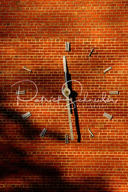 Photography of downtown Concord, NC, the largest city in Cabarrus County. Afternoon light dances across the the brick of an old clock on the wall of the Coltrane-Webb Elementary School in downtown Concord, North Carolina. Photo is part of a photographic series of images featuring Concord, NC, by Charlotte-based photographer Patrick Schneider..