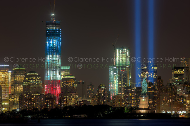 The twin beams of light of the Tribute in Light, an annual memorial to the events of September 11, 2001, shine into the evening sky in New York City over the skyline of lower Manhattan on Tuesday, September 11, 2012.  This view of the skyline includes two symbols of freedom, the Statue of Liberty and the Freedom Tower (One World Trade Center), under construction at the site of the original Twin Towers.  The Freedom Tower, lighted in the red, white, and blue colors of the American flag, is scheduled for completion in 2013.