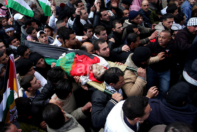 Palestinians carry the body of 23-year-old Talat Ramia during his funeral in the West Bank town of Al-Ram, near Jerusalem February 25, 2012. Ramia, a Palestinian protester who participated in clashes against Israeli soldiers near a checkpoint in the occupied West Bank on Friday died of a bullet wound, a Palestinian hospital official said. Photo by Issam Rimawi