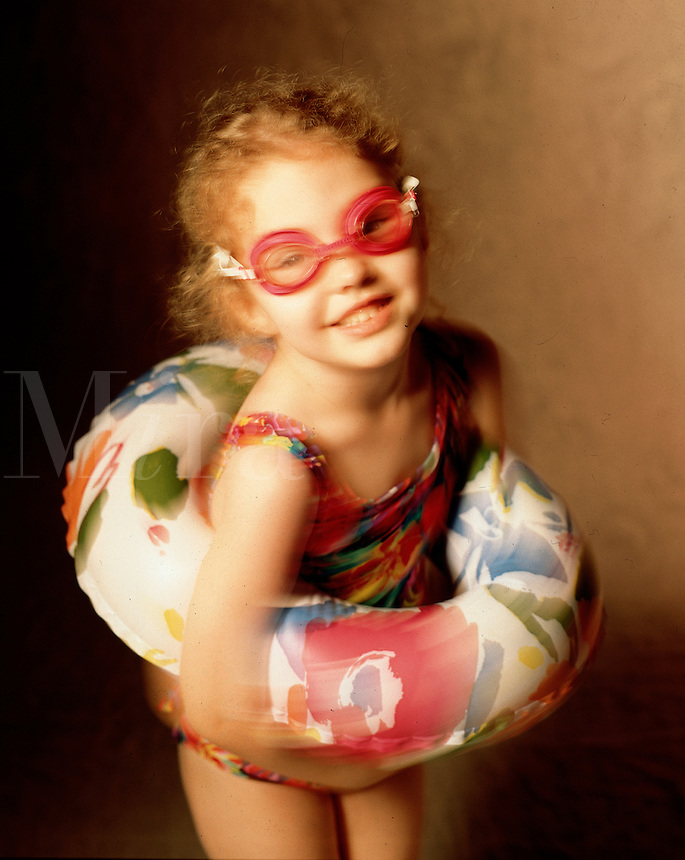 A 5 year old girl in motion wearing swimsuit, goggles and inner tube. Birmingham AL USA studio.