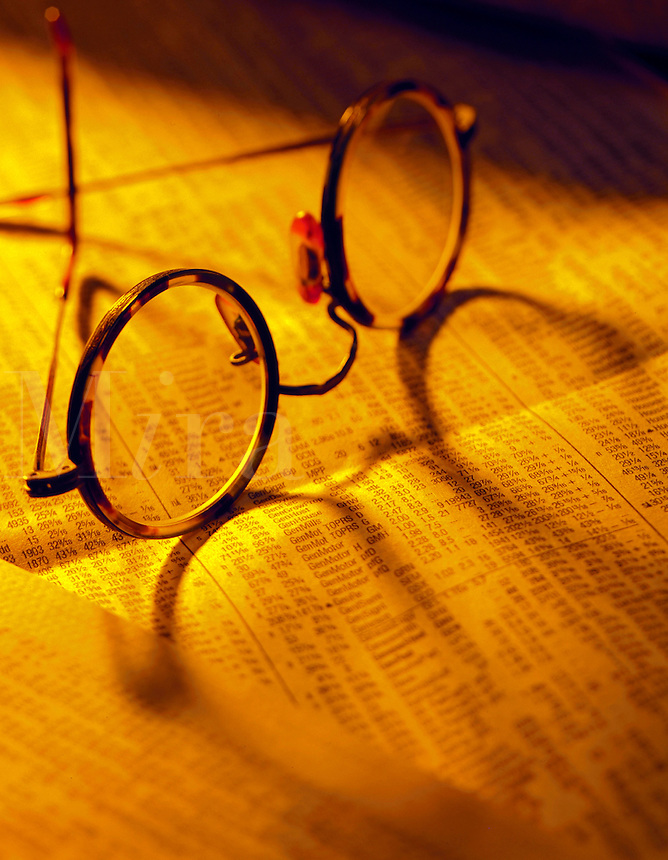 Eye glasses in warm lighting resting atop the financial section of a newspaper.