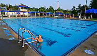 A woman pulls herself from the pool as the last adult to leave the water on the final day of summer swimming at an outdoor community pool.
