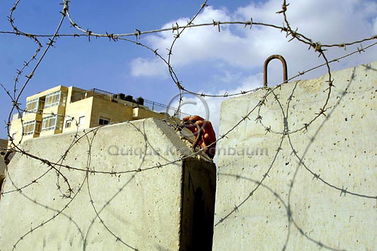 A Palestinian man tries to cross the wall built to separate the Palestinian territories from Israel, June 1,2003, in the West Bank neighbourhood of Abu Dis, next to Jerusalem.