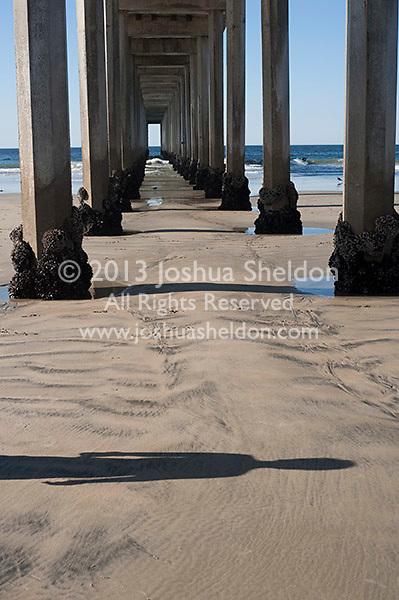 Person's shadow in sand in front of Scripp's pier, La Jolla, California