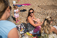"""A young woman breastfeeding her baby while sunbathing on the beach with a friend, and talking to another friend.<br /> Image from the breastfeeding collection of the """"We Do It In Public"""" documentary photography picture library project: <br />  www.breastfeedinginpublic.co.uk<br /> <br /> <br /> Hampshire, England, UK<br /> 03 /09/2013<br /> <br /> © Paul Carter / wdiip.co.uk"""