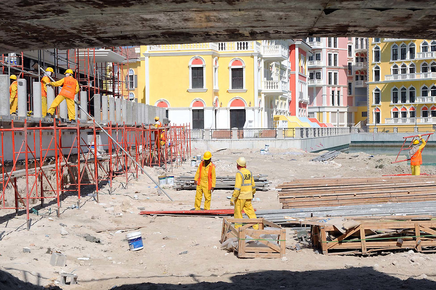 Doha Qatar novembre 2010. Operai al lavoro alla costruzione dello sviluppo immobiliare The Pearl. Una parte è liberamente ispirata all'architettura di Venezia. Men at work at the new real estate development The Pearl a part of which is freely inspired by Venezia's architecture.