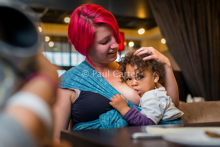 A mother  breastfeeding her toddler in a hotel restaurant.<br /> <br /> 13/06/2015