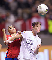 Abby Wambach, right, of the United States heads the ball in front of Wendy Acosta of Costa Rica during play in the CONCACAF Olympic Qualifying semifinal match at BC Place in Vancouver, B.C., Canada Friday Jan. 27, 2012. The United States won the match 3-0 to earn a berth in 2012 London Olympics.