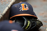 A Durham Bulls cap rests on top of a glove in the visitors dugout during the International League game against the Charlotte Knights at Knights Stadium on August 18, 2013 in Fort Mill, South Carolina.  The Bulls defeated the Knights 8-5 in Game One of a double-header.  (Brian Westerholt/Four Seam Images)