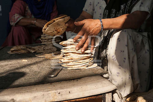 Amritsar, Punjab, India. Sri Harmandir Sahib Golden Temple. A woman stacks roti flatbreads in the free kitchen - langar - which feeds tens of thousands of people each day.