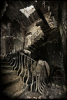 Ghostly figure of a soldier standing on the stairs of an abandoned building.