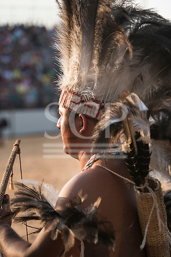 A chief watches the first ever International Indigenous Games, in the city of Palmas, Tocantins State, Brazil wearing an elaborate feather headdress and holding his bow. Photo © Sue Cunningham, pictures@scphotographic.com 24th October 2015