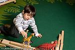 Education Preschool 3-5 year olds block play boy walking plastic toy giraffe animal on block construction horizontal
