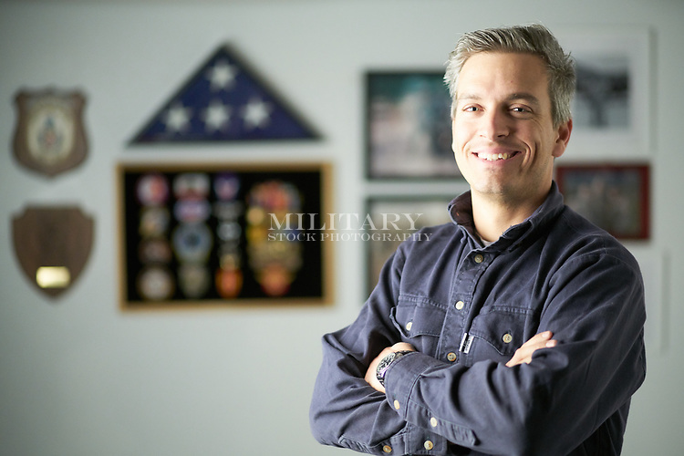 """Veteran at home with """"I love me"""" wall in background with photos and memorabila from time in military service,"""