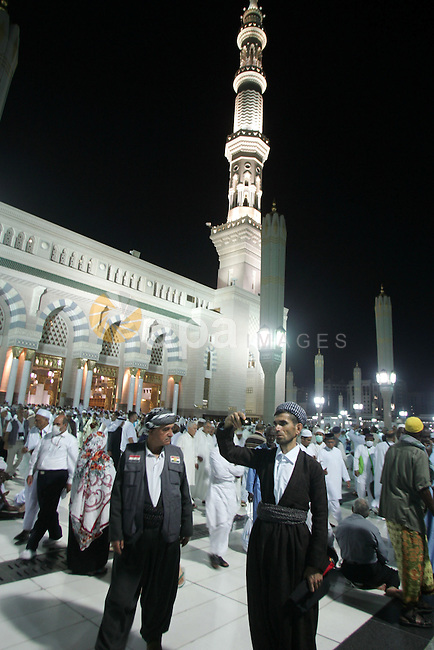 Muslim pilgrims walk outside the Prophet Mohammed Mosque in the Saudi holy city of Medina on November 4, 2010. More than three million Muslims are expected to converge on the holy cities of Mecca and Medina in western Saudi Arabia for the hajj. Islam's Prophet Mohammed is buried in Medina's landmark mosque, which is Islam's second holiest shrine after Mecca. Photo by Mahfouz Abu Turk