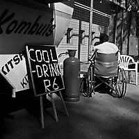 A man in a wheelchair outside a food stall on Van Beek Street, Ellis Park. Kombuis is an Afrikaans word meaning kitchen.