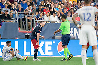 FOXOBOROUGH, MA - AUGUST 21: Referee Fotis Bazakos issues a yellow card against Tommy McNamara #26 of New England Revolution during a game between FC Cincinnati and New England Revolution at Gillette Stadium on August 21, 2021 in Foxoborough, Massachusetts.
