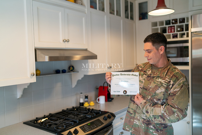 Proud off duty US in uniform soldier at home in his kitchen showing his diploma from online university, for sale as stock photography