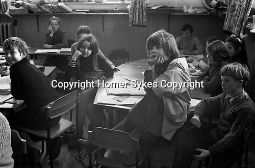Junior school, schoolboys and schoolgirls in class.  Young disabled schoolgirl wearing callipers or called leg braces. She cant turn easily in her chair to see the teacher who is talking to the class, so she is allowed to sit on the table. The braces are just visible sitting on her shared desk. A Scotland for World Cup Munich 1974 schoolbag is on the floor. Breasclete Isle of Lewis and Harris,   Outer Hebrides, Scotland. 1974.