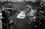 Junior school, schoolboys and schoolgirls in class, young disabled schoolgirl wearing callipers or leg The young girl is disabled she has braces - Caliper on one leg and cant turn easily in her chair to see the teacher who is talking to the class, so she is allowed to sit on the table. The braces are just visible sitting on her shared desk. A Scotland for World Cup Munich 1974 schoolbag is on the floor. Breasclete Isle of Lewis and Harris,   Outer Hebrides, Scotland. 1974,
