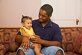 MR / Schenectady, NY. Father (22, African American) looks with pride at his infant daughter (girl, 10 months, African American & Caucasian). MR: Dal7, Dal4. ID: AL-HD. © Ellen B. Senisi