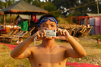 Chinese tourist taks a photo with his SONY digital camera at a beach by the Li River opposite Guilin city centre in Guilin, China. Sony continued to hold onto its number 2 spot in China's digital camera market..