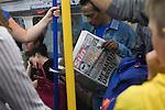 Man reading the Sun newspaper on London Underground Uk 2010.