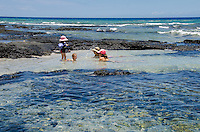A local girl and boy with their mothers enjoy a sunny day playing in tide pools at a beach in Puako, South Kohala, Hawai'i Island.
