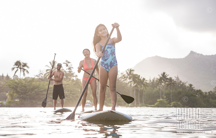 A family has fun learning how to standup paddle on Wailua River, Kaua'i.