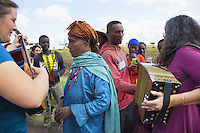 """Ethiopia. Southern Nations, Nationalities, and Peoples' Region. On the road to Sodo. Janik Michon (L) with the guitar and Chantal Marguerie (R) with accordion play music to a group of ethiopian farmers met along the road during a bus stop. Marc Vella is a french musician and a nomadic pianist. Over the last 25 years he has travelled with his Grand Piano in around forty countries to celebrate humanity. Creator of """"La Caravane amoureuse"""" (The Caravan of Love) he takes people with him to say """"I love you"""" to others and """"lovingly conquered"""" their hearts and souls. The Omo Valley, situated in Africa's Great Rift Valley, is home to an estimated 200,000 indigenous peoples who have lived there for millennia. Southern Nations, Nationalities, and Peoples' Region (often abbreviated as SNNPR) is one of the nine ethnic divisions of Ethiopia. 5.11.15 © 2015 Didier Ruef"""
