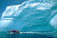 Small boat of sightseers motoring past an enormous intricately patterned iceberg in Half Moon Bay Antarctica