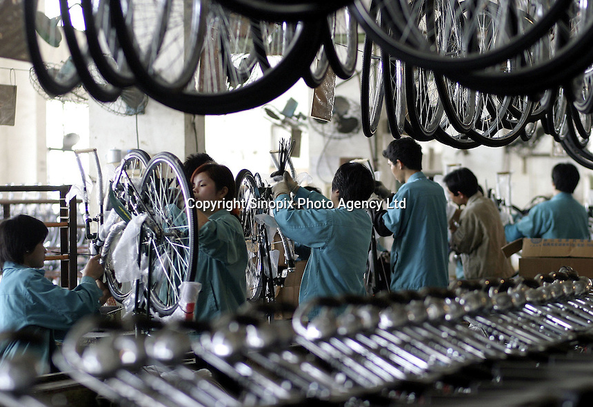 Workers on the assembly line at the Shanghai Forever Bicycle Factory (SFBF) in Shanghai, China. Despite the government's efforts to encourage automobile ownership in recent years, the bicycle remains the most popular mode of transportation for China's masses. The SFBF, it's products once a must have and a symbol of status for every Chinese family, are now supplying bicycles to countries around the world. It has seen it's sales increase 59% percent in the past year to 876 million yuan (euro 89.36 million)..21-APR-04