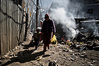 A woman miner walks with her child along the burning garbage pile in the street of La Rinconada, Peru, 5 August 2012. During the last decade, the rising price of the gold has attracted thousands of people to La Rinconada in the Peruvian Andes. At 5300 metres above sea level, nearly 50.000 people work in the gold mines and live in the nearby colonies without running water, sewage system or heating service. Although the work in the mines is very dangerous (falling rocks, poisonous gases and a shifting glacier), the majority of miners have no contract and operate under the cachorreo system - working 30 days without payment and taking the gold they supposedly find the 31st day as the only salary. In spite of a demaged environment, caused by mercury contamination from the mining and the lack of garbage disposal, people continue to flock to the region hoping to find their fortune.
