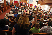 ANDREW SHURTLEFF/THE DAILY PROGRESS <br /> A woman raises her hand to the harmonies of choir during the Unity Days Interfaith Service at the First Baptist Church. The service honored and remembered those who recognize the past racial and economic inequities and who stand up to the racism and hate of white supremacy.