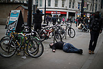 © Joel Goodman - 07973 332324 . 06/04/2017 . Manchester , UK . A man lies flat out on the pavement on Piccadilly Gardens . An epidemic of abuse of the drug spice by some of Manchester's homeless population , in plain sight , is causing users to experience psychosis and a zombie-like state and is daily being witnessed in the Piccadilly Gardens area of Manchester , drawing large resource from paramedic services in the city centre . Photo credit : Joel Goodman
